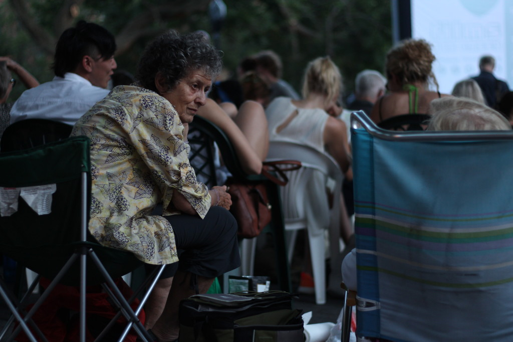 "A lady in conversation at Tompkins Square Park on July 5, 2013, waiting to see the French film ""L'Arnacoeur."""